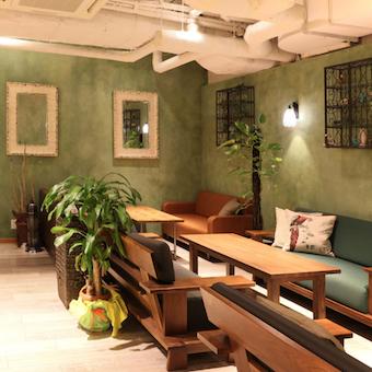 壁や観葉植物の緑がリラックスできるアンティーク風な店内。