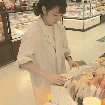 一つ一つ丁寧に商品整理をします。白衣を着た姿はお菓子の研究員!